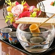 瓶から杯へ竹の杓で汲む日本酒。一輪の花を添えて…