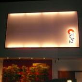 アール型の壁に灯が灯り、目にはおどろく大きな看板と坪庭