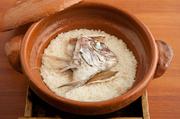 お米マイスターが選定する米、天然真鯛、昆布出汁、天日塩だけで仕立てる『鯛めし』。特注の信楽焼の土鍋を使い、生米から炊きあげます。提供までに40分ほどかかります。