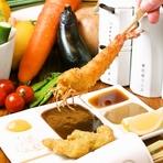 カウンター席に置かれた鯉のぼりは、食べ終えた後の串を入れる串さし。可愛らしいデザインに心が温まります。白磁の器に映えるトッピング付きの串カツ。メインで使用されている食器は、お店オリジナルデザインです。