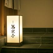 ビルの上階でひっそり灯る行灯と、風情ある引き戸が印象的