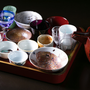 お酒の味わいを左右する酒器は、お好みのものを選択できます。酒器に限らず、器や皿も、骨董から作家物まで、店主の目で選んだこだわりの逸品が揃っています。
