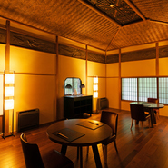 見事な網代天井、繊細な彫刻、塗り壁など日本家屋らしさの中に、モダンな照明や丸いテーブルなどがセンス良く使われています。テーブル席は、年配の方も利用しやすいと評判。