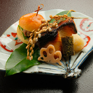コースの一品イメージ(天然鰤の西京焼き イノシシバーガー)。旬の食材をいち早く取り入れた、創意工夫に富んだ一品の数々。 大将がその日おすすめするお料理をおまかせコースとしてご披露いたします。
