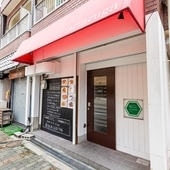 建物の1階で赤いテントと緑の亀の看板が目印です