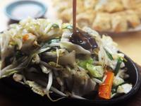 熱々の鉄板に乗せられた野菜炒め。他店とは一味違うこだわりメニュー。