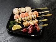 帆立、いいだこ、つぶ貝、さざえの4種。一皿に2本のって1人前。串を外せば皆とシェアできる便利な一品。