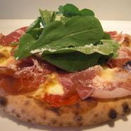 チーズとトマトソースの上に生ハムとルッコラを乗せたピッツァです