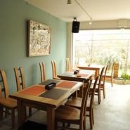 ゆったりとした無垢のテーブルと椅子の置かれた店内からは 向山公園の緑が一面の窓に広がる癒しの空間。