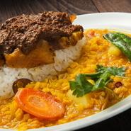 スパイスに漬け込んだ宮崎赤鶏は刺激的な辛さ。香菜風味のまろやかなダルカレーとの相性抜群。