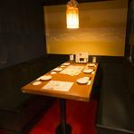 両側ソファのテーブル席。間接照明のもと、楽しげな会話がこだましています。