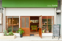 グリーンと木枠のドアが引き立つ、カフェのようなエントランス