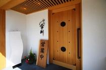 品格あふれるエントランス。白壁に木製のドアが引き立ちます