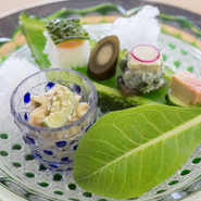 地元の味がじっくり楽しめる『前菜』ミミガ-の胡麻酢和えゴーヤの寿司など五味五色で味わえる一品。ゴーヤで作られた器に彩られた料理。清涼感と地元の味が口の中に広がります(期間限定会席に含む)
