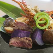 ロブスター、紅イモ、国産牛、椎茸、ゴーヤなど素材をダイナミックに焼き上げ調理。熱々の石に月桃の葉をのせて香りと共に楽しめる一品です。(期間限定会席に含む)