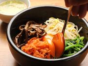 牛すじや野菜を煮込んでつくったスープを好みの量かけて味わいます。自家製のナムルが上にのっています。