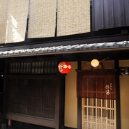 店の外観は、祇園の町並みに溶け込んだ風情あふれる京町家。引き戸にかけられた臙脂色の暖簾と、小さな提灯が目印です。