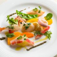 新鮮なボタンエビやホタテなど、旬の魚介が6種類ほど。季節の野菜と合わせた、やさしい色合いの一皿です。