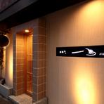 木のぬくもりを感じさせる外装に、黒地に白、赤いワンポイントが効いたのお店のロゴがお洒落な外観。美しく飾られた竹と日本酒の飲み頃を知らせる杉玉が、くつろぎ空間へと誘ってくれます。