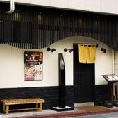 白い壁に黒の格子がモダンな外観。格子戸の先は落ち着いた和空間