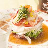 マグロ、ブリ、ホタテ貝柱、イクラ、甘エビなど、その日仕入れた新鮮な魚介類を使ったサラダ。サニーレタス、トマト、カイワレなどの生野菜の彩りが美しい。純正ごま油を使った自家製の中華ドレッシングを添えて。