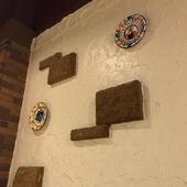 荒く塗られた壁に絵皿がかかげられています