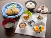 写真は春キャベツのメンチカツと、卵の袋煮、自家製胡麻豆腐など小鉢5品とお漬物、お味噌汁のメニュー。お料理はどれも季節の素材を生かしたやさしい味わい。飛鳥棚田米のもっちりしたご飯の味を引き立てます。