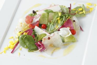 お花畑のような盛り付けの野菜を魚と一緒に『旬のお造りサラダ』