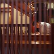清水寺へと続く五条坂や祇園から徒歩圏内ながら、静けさ漂う渋谷通に面する京町家。店内は白い壁や赤いクロスの椅子、どこか女性的な桜の木のカウンターなどを配し、岡本さんの人柄を感じさせる明るく寛いだ雰囲気。