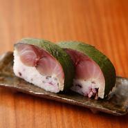 鯖と相性の良いすぐき(酸茎)を合わせて。シャリに茎を混ぜ、全体を葉で巻きます。夏には本しば漬けと紫蘇の葉で。
