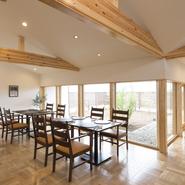 白と茶を基調とした開放感の感じられる広い空間。大きな窓ガラスからは明るい光が差し込みます。素材や使い勝手の良さでオーナーがセレクトした木のテーブルや椅子がすっきりと配されています。