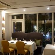 店内は絨毯を贅沢に敷き詰め、イタリアの家具メーカーマルケッティの椅子がさらなる非日常空間を演出。ランチタイムは壁一面のガラス窓から陽光が降り注ぎ、夜はライトアップされた緑がおしゃれな空間を演出します。