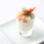 コース料理の最初の楽しみとなるアミューズは、旬の選りすぐりの食材を使ってインパクトのある味わいに。レンズ豆と生クリームを合わせたやさしい食感のムースに、その日の仕入れに応じた新鮮な魚介を合わせます。