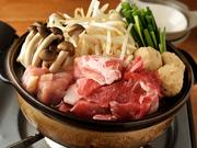 たっぷりの豚肉につくねと野菜。ボリューム満点に見えますが何とこれで1人前。【居酒屋いっぱち食堂】の鍋は1人前から注文できるので人気です。自家製出汁は醤油か味噌チゲを選べます。