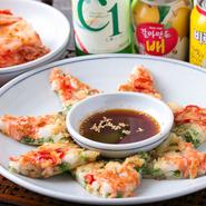 韓国の定番家庭料理と言えば『チヂミ』です。日本のお好み焼きと似ている料理で、小麦粉や米粉、たまごを混ぜた生地に、ニラや玉ねぎなどを入れて焼いた一品です。特製のタレをつけて食べればお酒がすすみます。