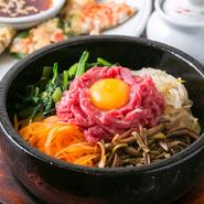 韓国の混ぜご飯のことで、石の器にご飯やナムル、キムチ、肉、たまごなどを入れて食べる料理です。おこげも美味しいので、具材とご飯をすべて混ぜ、石の熱で少し焦がしてから食べるのがおすすめです。