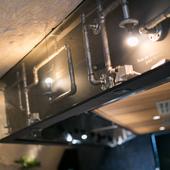 カウンター上の下がり壁にはむき出しのパイプのオブジェが