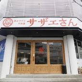真っ白な看板に赤く書かれた店名が目印