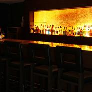 【スカイダイニング 彩風】のカウンターバーが、隣接。ウエイティングバーや食後のお酒を愉しむ人によって、和やかな空気に包まれています。ワインやオリジナルカクテルを、一杯いかが。