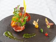 活きたままのオマール海老がそのまま調理されるプリプリ食感のオマールエビの一皿は、オードブル又は魚料理として供される人気メニュー。1つ1つの小さな野菜たちも本来の旨味が充分に引き出され楽しませてくれます。