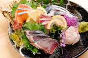 毎日市場の鮮魚店から直送される旬魚を贅沢に一皿で。真の王道盛り合わせはこれで決まりです。サーモン、タイ、旬魚、カツオのタタキ、しめ鯖が定番。画像の鮮魚はブリです。