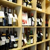 説明書きが付いたボトルが並ぶ、ワインセラー