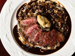 スパイスの効いた真っ黒『ステーキのせカレー』は、ランチタイムの人気メニュー