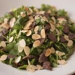 香菜は元々ヨーロッパが原産地で、種子をスパイスとして使うが、かつてのフランス領インドシナから生葉を食べる文化が逆輸入された。燻製した砂肝とアーモンドの組み合わせを考案した開店以来の看板料理。