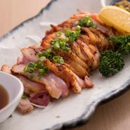 佐賀県の自然豊かな山間部で長期飼育されている鶏「みつせ鶏」を使った『みつせ鶏のたたき』は、柔らかくて弾力のある風味豊かな人気メニュー。皮面をカリッと炙ってたたいた逸品です。