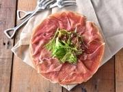 丸太の上に敷き詰められた、熟成生ハム「ハモンセラーノ」。鮮やかなピンク色でさっぱりとした味わいと柔らかな食感が特徴。