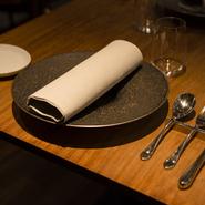 料理がシンプルな分、気を遣うのがテーブルウェアです。お皿はフランスのリモージュ地方の磁器などを使い、料理の美しさを引き立てます。肉料理のカトラリーにはフランスのラギオールを使用します。