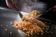 【鉄板焼 金葉亭】の『ガーリックライス』は、約1ヶ月熟成させた秘伝のニンニク醤油ダレがポイントです。炒めている最中、何度かに分けてタレをかけ直し、ご飯に充分染み込ませ、パラパラに香ばしく仕上げます。
