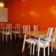 オレンジ色の壁の横には、オフホワイトのテーブル席。女性がちょっと立ち寄り、喉を潤しお腹を満たすにはぴったり。ポップな色彩とベーシックな色合いのコントラストも心地良く、女子会を開きたくなります。