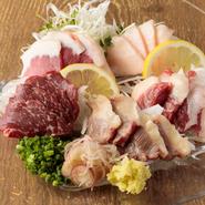 熊本から店舗へ直送の新鮮な状態の馬肉を刺しとして提供してくれます。添え物の刻みネギや生姜、ミョウガをお好みで合わせていただくと、またさらに違った味わいが楽しめます。(写真は扱ってる馬刺の一部です)